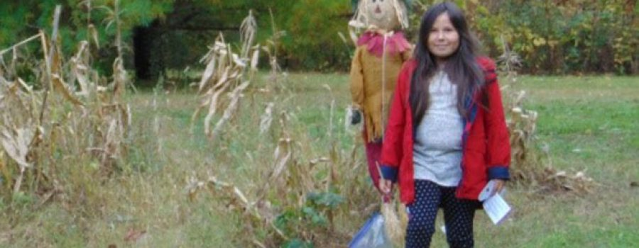 child with scarecrow
